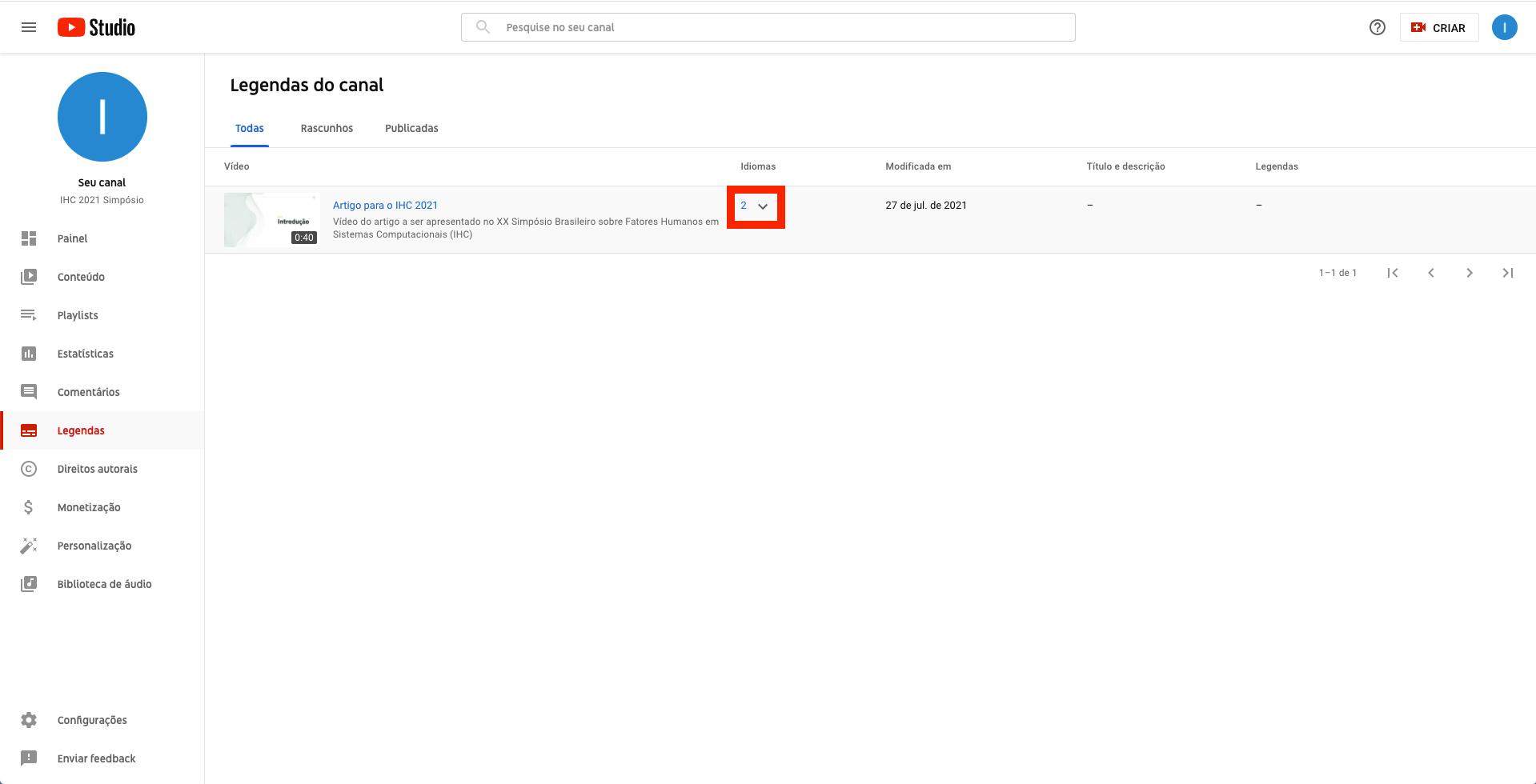 Captura de tela do YouTube Studio. Página de legendas do canal, com destaque para o ícone de seta que permite expandir as opções de idioma do vídeo listado